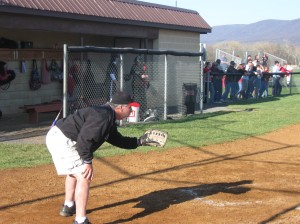 Coach Hunt filling in while the catcher gets ready