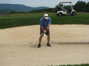 Owner for the Night Dennis Cerrie hitting from a fairway bunker.